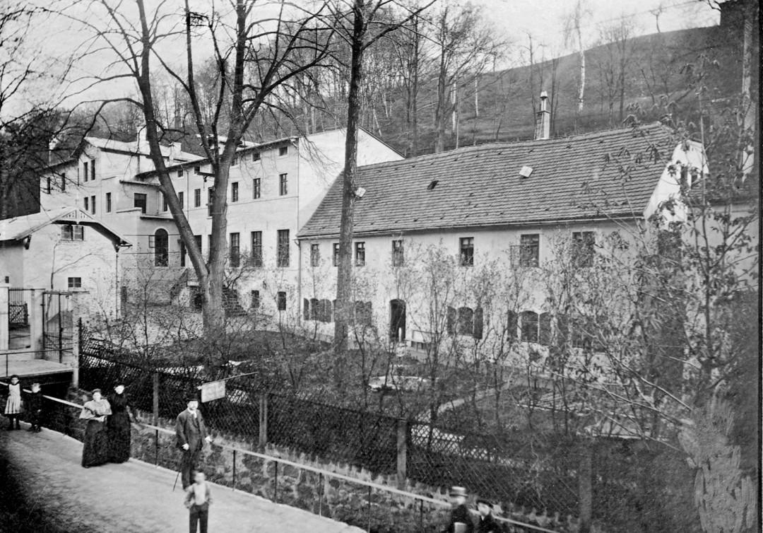 Die Tintenfabrik im Loschwitzgrund 1891 mit dem neu errichteten Fabrikgebäude im Hintergrund. Der Mann mit Melone könnte Eduard Leonhardi sein. Foto: Jubiläumsalbum (Archiv Leonhardi-Museum)