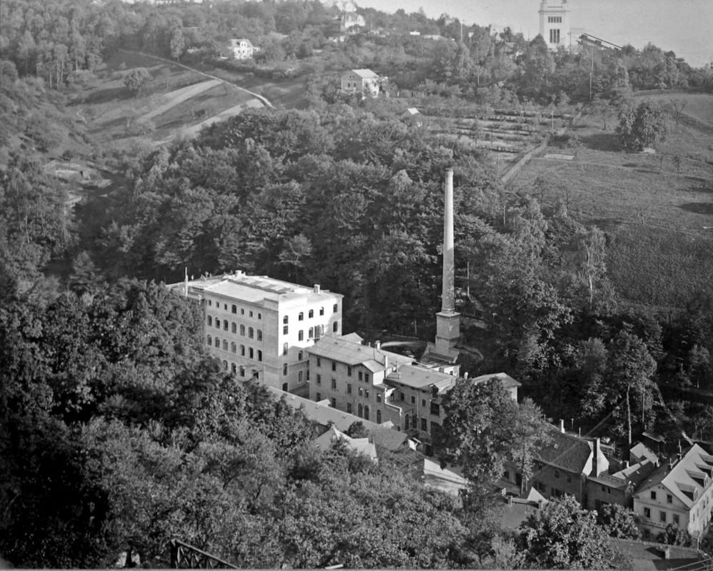 """Die Tintenfabrik im Jahr des 75-jährigen Bestehens 1901 mit dem """"Jubiläumshaus"""" (links) und dem 35 Meter hohen Schornstein. Im Hintergrund ist die neu errichtete Bergstation der Schwebebahn zu erkennen. Foto: Jubiläumsalbum (Archiv Leonhardi-Museum)"""
