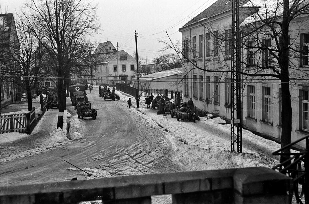 Wehrmachtssoldaten auf der Hutbergstraße zwischen Gasthof und Schule um 1943. Im Hintergrund auf dem Schulhof ist ein großes Zelt zu sehen, worin vermutlich Soldaten einquartiert waren. Dazwischen läuft ein Kind zur Schule.  Foto: Sammlung Karl Richter