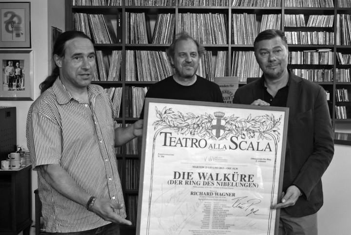 """René Pape stellte drei Plakate von Aufführungen in der Mailänder Scala mit den Unterschriften der Künstler für eine Versteigerung für die Flutopfer zum Elbhangfest zur Verfügung. Eines ersteigerte für 1.300 Euro der """"Sweetwater Recordstore"""" in Loschwitz. René Pape (rechts) übergab das Plakat Tino Tuch persönlich, bei dem es jetzt zentral im Laden hängen wird. Götz Wenzel (links), Schatzmeister des Elbhangfest e.V., konnte das Geld in Empfang nehmen. Foto:Jürgen Frohse"""