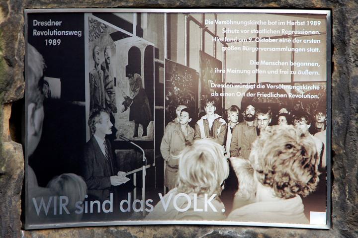 Diese fotodokumentarische Erinnerungstafel an der Außenmauer des Gemeindezentrums Versöhnungskirche zeigt eine Vernissage von 1988 (am Mikrofon Pfarrer Andreas Horn). Foto: Stefan Behr